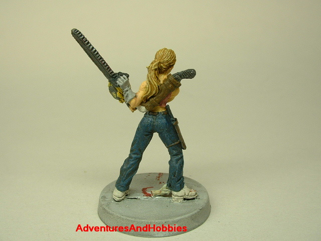 Zombie survivor woman with chainsaw painted figure for role-playing games and table top war games rear view